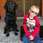 Caleb is sitting on his front step next to Autism Support Dog Cory, a black Labrador