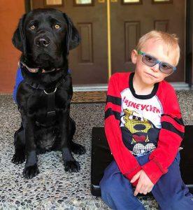 Caleb sitting next to Autism Service Dog Cory