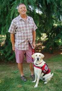 James standing with PTSD Service Dog Andy