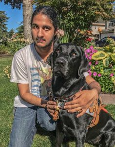 Jashandeep sits alongside his Guide Dog Pebbles