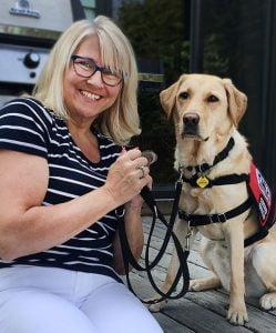 Patti sitting next to PTSD Service Dog Tiaa